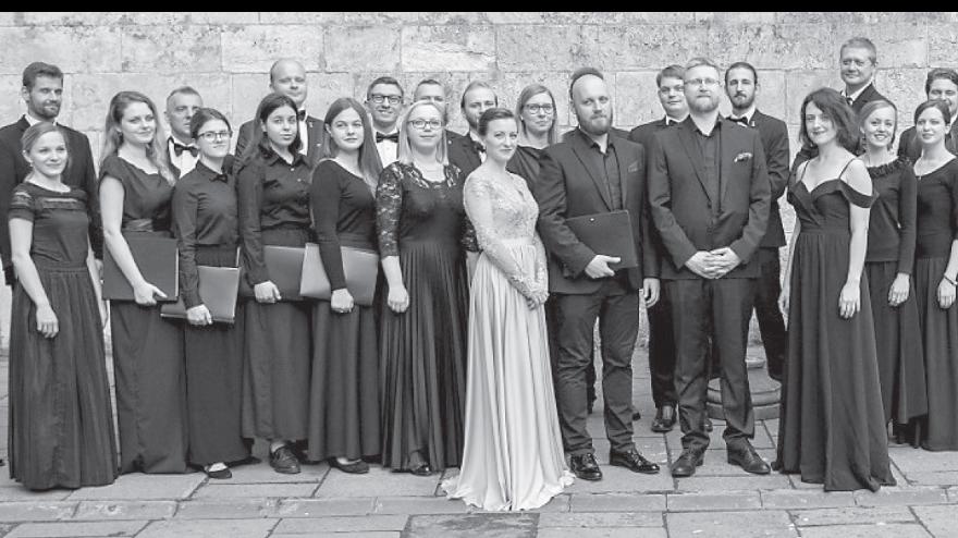 Zdjęcie chóru, kilkanaście osób w eleganckich ciemnych strojach stoi w zwartej grupie