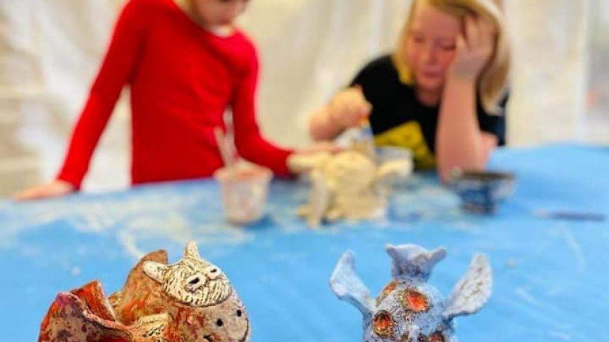 2 gliniane stworki na stole z niebieskim obrusem, w tle 2 dzieci formujących glinę