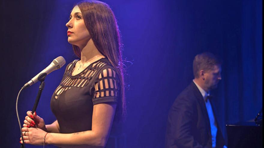 Postać kobiety na scenie z mikrofonem, w tle postać pianisty